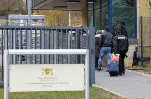 Sicherheitsbesamte kontrollieren das Gepäck der Flüchtlinge, die in die Lea Ellwangen kommen. Foto: dpa