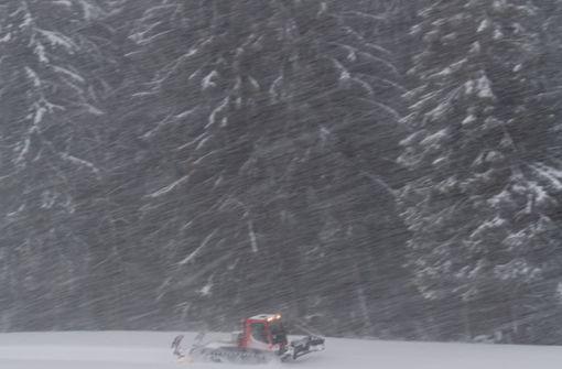 Hinterzarten: Ein Pistenbully fährt bei dichtem Schneetreiben an Bäumen vorbei und spurt eine Langlaufloipe.  Foto: dpa