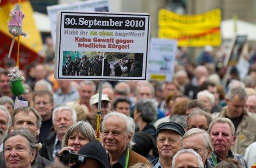Stuttgart 21-Gegner halten am 29. September auf dem Schlossplatz in Stuttgart während einer Kundgebung Plakate und Transparente in den Händen. Mehrere tausend Menschen demonstrierten gegen den ungewöhnlich harten Polizeieinsatz. Foto: dpa