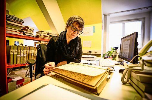 Gesa Grimme blättert in einem Inventarbuch des Lindenmuseums. Foto: Lichtgut/Leif Piechowski