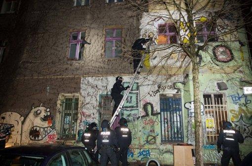 Elite-Polizisten dringen über eine Leiter in ein Haus im Berliner Stadtteil Friedrichshain ein, wo sich Gewalttäter verschanzt haben. Foto: dpa