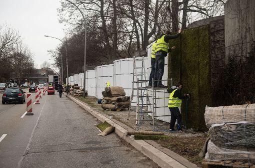 Das Moos wird an den Trägergerüsten längs der Straße angebracht. Foto: dpa