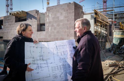 Silke Koch und Rüdiger Arendt zeigen auf der Baustelle des neuen Olga-Viertels den Plan ihres künftigen Heims. Das nimmt bereits Konturen an (siehe hinten). Foto: Lichtgut/Achim Zweygarth