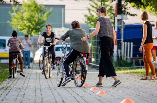 Erste Gleichgewichtsversuche auf dem Gepäckträger: Eine Caritas-Mitarbeiterin unterstützt eine Teilnehmerin des Projekts Bike Bridge. Foto: Lichtgut/Christoph Schmidt
