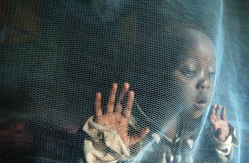 Die dreijährige Siama Marjan steht in Nairobi (Kenia) hinter einem Moskitonetz, das sie vor dem Stich von Malaria-Mücken schützt. Foto: dpa
