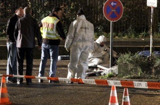 Beamte der Kriminalpolizei stehen am Freitag nach einem Banküberfall mit zwei Toten in der Nähe des Tatorts. Foto: dapd