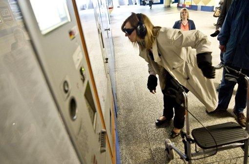 Bürgermeisterin Isabel Fezer macht den Selbstversuch im gerontologischen Anzug, der das Altsein simuliert. Beim Fahrscheinkauf hat sie große Probleme. Foto: Max Kovalenko