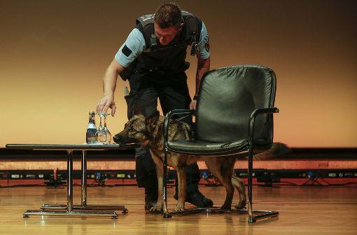 Sicherheit geht vor: Bevor der prominente Besuch eintrifft, inspiziert ein Spürhund der Polizei die Halle – samt den Gläsern der Moderatoren auf der Bühne. Foto: Lichtgut/Piechowski