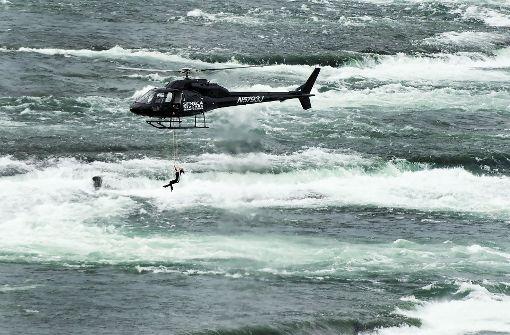 Akrobatin baumelt an Zähnen von Hubschrauber