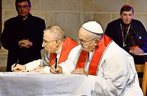 Papst Franziskus (rechts) und der Präsident des Lutherischen Weltbundes, Bischof Munib Younan, unterzeichnen  in der Kathedrale von Lund ein gemeinsames Wort anlässlich des katholisch-lutherischen Reformationsgedenkens Foto: epd