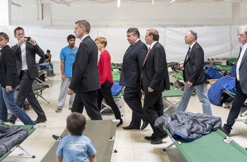 Bundeswirtschaftsminister Sigmar Gabriel (M., SPD) geht  durch eine Notunterkunft für Flüchtlinge im ehemaligen Praktiker-Baumarkt in Heidenau. Foto: dpa