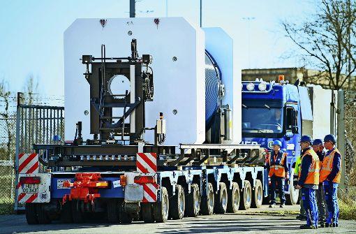 Im Schritttempo rollt ein  Lastwagen mit einem Castor ans Ufer. Foto: dpa