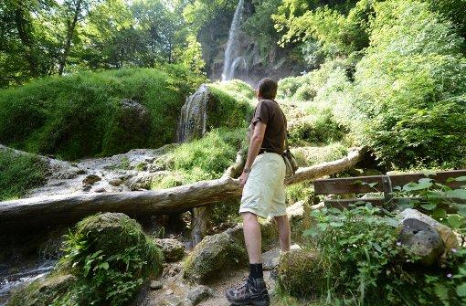 Ein Wanderer ist am Uracher Wasserfall unterwegs. Foto: dpa
