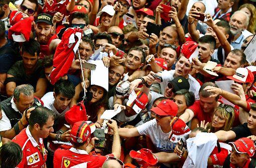 Beliebt und bedrängt: Sebastian Vettel stellt sich gern der Ferrari-Fangemeinde. Foto: AFP