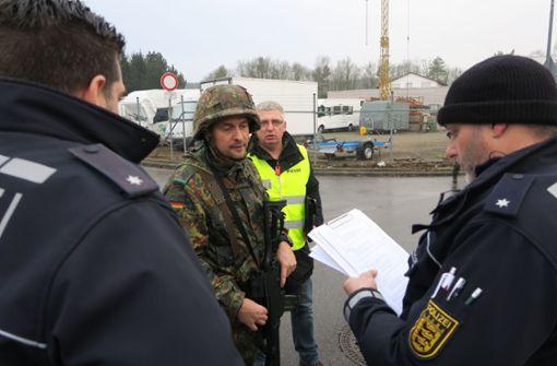 Während der Gruppenführer Bastian Essers mit  Polizisten spricht, kommt Bernd Winkler (Dritter von links) auf sie zu. Er spielt einen Journalisten, der just während der Übergabe des Verdächtigen Fragen stellen will. Foto: Malte Klein