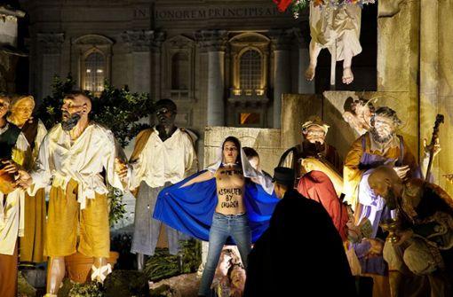 Barbusige Femen-Aktivistin in Weihnachtskrippe