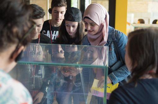 Die Syrerin Hala Twin (mit Kopftuch) mit einer Schulklasse vor einer Vitrine im Haus der Geschichte. Foto: Lichtgut/Max Kovalenko