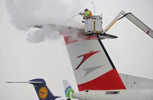 Ein Vorfeldmitarbeiter enteist am Samstag auf dem Bodensee Airport in Friedrichshafen eine österreichische Passagiermaschine. Bei Minusgraden ist das Enteisen notwendig, damit die Ruder der Maschine beweglich bleiben. Foto: dpa