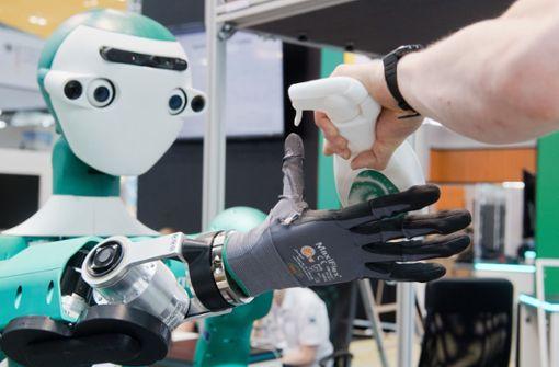 Kollege Roboter und Mensch arbeiten zusammen. In Zeiten von künstlicher Intelligenz und Vernetzung ändern sich auch die Jobs. Künftig sind unter anderem verstärkt Spezialisten für Datenschutz gefragt. Foto: dpa