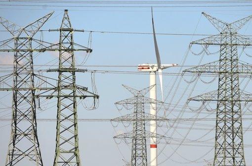 Windrad vor Hochspannungsleitung – die Netze kosten viel Geld. Das könnten auch die Stromkunden zu spüren bekommen Foto: dpa