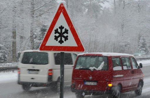 Schneebedeckte Autos fahren am Freitag in Stuttgart. Foto: dpa
