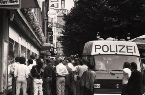 Fußballfans bei der EM 1988 vor einem Schaufenster in der Fußgängerzone der Königstraße – Polizeibeamte fahren heran und schauen auch mit zu. Foto: Thomas Hörner
