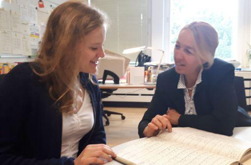 Was für ein Schüler war Fritz Bauer? Das Zeugnisbuch gibt Anna Luisa Karl (links) und Schulleiterin Karin Winkler Foto: Eva Funke