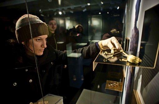 Die Konservatorin Kati Bott bestückt eine Vitrine mit goldenen Kleiderspangen Foto: Lichtgut/Max Kovalenko