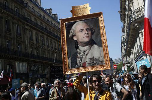 Demonstranten tragen ein Foto von Emmanual Macron als König Louis XVI durch die Straßen von Paris. Sie sehen Parallelen zu dem ungeliebten Monarchen vor über 200 Jahren. Damals löste die Demokratie die Monarchie ab.  Foto: AP