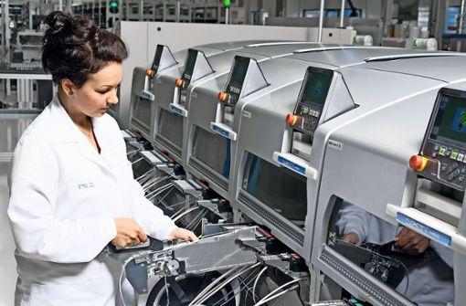 Eine Pilz-Mitarbeiterin bestückt eine sogenannte SMD-Linie  mit neuen Elektronikbauteilen. Foto: Pilz