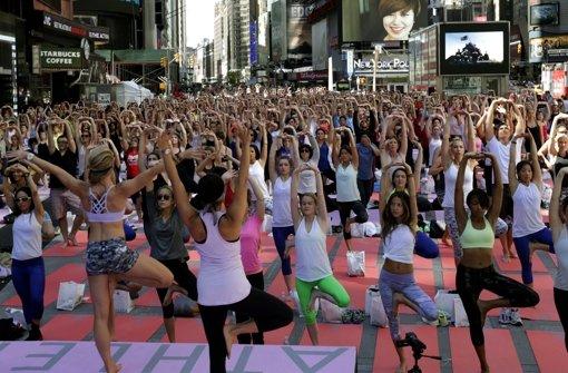 Es begann mit nur drei Teilnehmern, mittlerweile machen Tausende Menschen mit: Mit Yoga-Übungen läuten die New Yorker auf dem Times Square den Sommer ein – völlig entspannt. Was Yoga für den Rücken bringt, lesen Sie hier. Foto: EPA