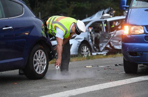 Ein Polizist markiert an einem Unfallwagen die Spuren. Das Material, das am Samstag sichergestellt wurde, müssen die Beamten vom Verkehrskommissariat jetzt auswerten. Foto: dpa