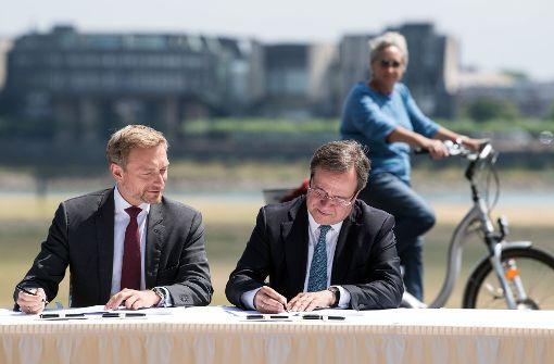 Politidylle Christian Lindner und Armin Laschet unterzeichnen unter den Augen einer interessierten Bürgerin den Koalitionsvertrag