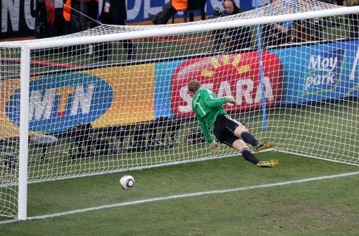 WM 2010: Der deutsche Nationaltorwart Manuel Neuer steht in der Luft und sieht den Ball hinter sich auf den Boden fallen. Der Schuss des englische Spielers Frank Lampard kommt hinter der Linie auf, der Schiedsrichter lässt aber weiterspielen. Foto: dpa