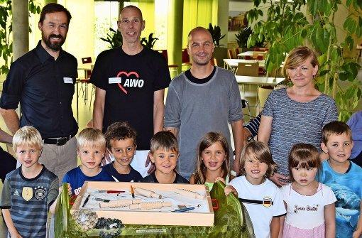 Einige Kindergartenkinder, der Kindergartenleiter Marco Schwender (Zweiter von rechts) und die Elternbeirätin Jutta Schneider haben den Sandkasten an den Pflegeheimleiter Thomas Burghoff (links) und den Awo-Mitarbeiter Michael Hama übergeben. Foto: Alexandra Kratz