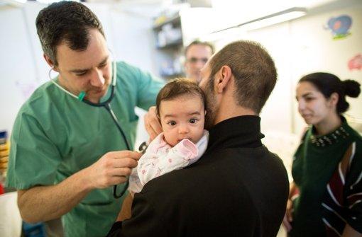 Der Arzt Maximilian Pelzer (links) untersucht in Berlin in einer Flüchtlingsnotunterkunft im ehemaligen Flughafen Tempelhof im Medical Center ein Flüchtlingskind aus Mazedonien auf dem Arm des Vaters. Foto: dpa