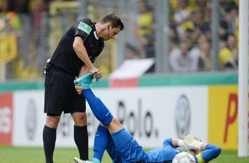 Kämpfen bis zum Krampf: Rielasingens Torwart Dennis Klose wird von Schiedsrichter Christian Dietz geholfen.  Foto: dpa