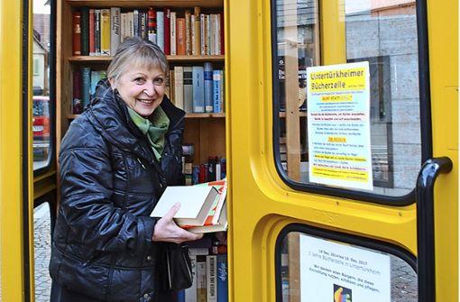 Marlene Blumenstock schaut in der Untertürkheimer Bücherzelle – eine ihrer erfolgreichen Aktionen – regelmäßig nach dem rechten. Foto: Elke Hauptmann