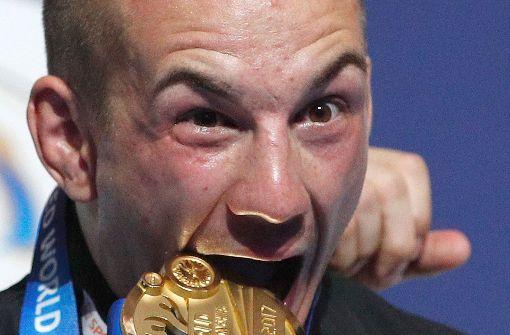 Gold! Frank Stäbler beißt zu und prüft wohl, ob es echt ist. Foto: dpa