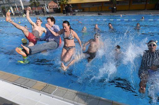 Etwa 30 hartgesottene Schwimmer haben am Freitagmorgen mit einem Sprung ins warme Wasser des Karlsruher Sonnenbades die Freibadsaison eröffnet. Foto: dpa