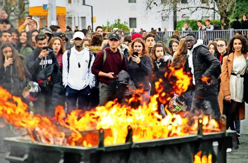 Schüler stehen hinter einer brennenden Mülltonne. Foto: AP