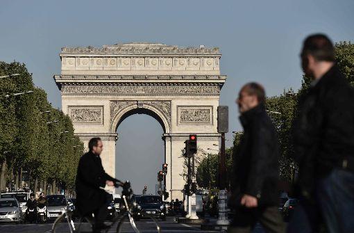 Einen Tag nach den Schüsse auf dem Boulevard Champs-Élysées in Paris überqueren wieder Fußgänger die belebte Straße. Foto: AFP